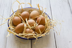 Fresh eggs in enamel bowl on wood background Stock Photos