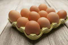 Fresh eggs in a green ceramic holder on rustic background Stock Photography