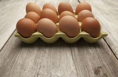 Fresh eggs in a green ceramic holder on rustic background Stock Images