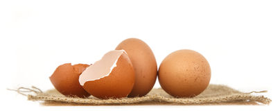 Fresh eggs and half of eggshell on white background Stock Images