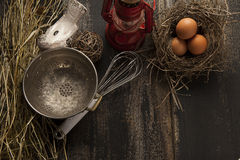 Fresh eggs and kitchen tools. Fresh eggs in a nest along with rustic kitchen tools on a rustic background Stock Photography
