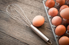 Fresh eggs and metal whisk Stock Images