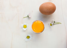 Fresh eggs. Fresh organic eggs whole and raw yolk. Some daisies on a wooden surface Royalty Free Stock Photos