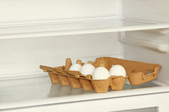 Fresh eggs in a paper box on refrigerator shelf. Royalty Free Stock Images