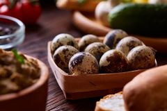 Fresh eggs of a quail with greens and vegetables on wooden table, selective focus, close-up Stock Photo