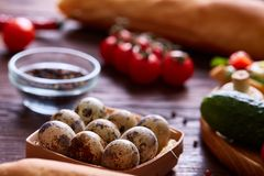 Fresh eggs of a quail with greens and vegetables on wooden table, selective focus, close-up Royalty Free Stock Photo