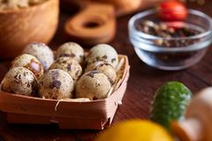 Fresh eggs of a quail with greens and vegetables on wooden table, selective focus, close-up Royalty Free Stock Images