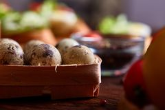 Fresh eggs of a quail with greens and vegetables on wooden table, selective focus, close-up Stock Photos