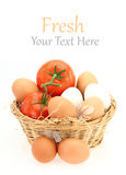 Fresh eggs and tomatoes in the basket Royalty Free Stock Photos