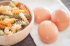 Fresh eggs on wooden plate with fusili Stock Images