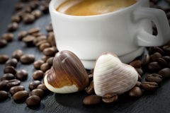Fresh espresso, coffee beans and chocolate candies Royalty Free Stock Photos