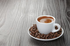 Fresh espresso with coffee beans in saucer on wood Royalty Free Stock Photos
