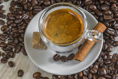 Fresh espresso coffee with sugar, cinnamon and lot of beans Royalty Free Stock Photos