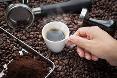 Fresh espresso cup. Fresh espresso. Hand grabbing an ear cup of of hot espresso coffee also see an espresso machine group head, coffee tamper and ground coffee Stock Photography