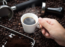 Fresh espresso cup in hand. Hand grabbing an ear cup of of hot espresso coffee also see an espresso machine group head, coffee tamper and ground coffee lay on Royalty Free Stock Photos