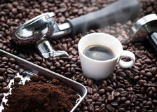 Fresh espresso cup. A cup of hot and fresh espresso coffee lay on many roast coffee beans also see an espresso machine group head, coffee tamper and ground Royalty Free Stock Photography