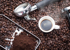 Fresh espresso cup. A cup of hot and fresh espresso coffee lay on many roast coffee beans also see an espresso machine group head, coffee tamper and ground Stock Photo