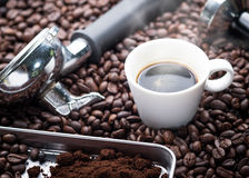Fresh espresso cup. A cup of hot and fresh espresso coffee lay on many roast coffee beans also see an espresso machine group head, coffee tamper and ground Royalty Free Stock Images
