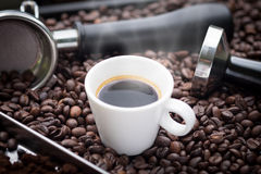 Fresh espresso cup. A cup of hot and fresh espresso coffee lay on many roast coffee beans also see an espresso machine group head, coffee tamper and ground Royalty Free Stock Photos