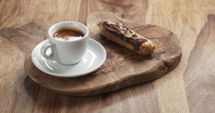 Fresh espresso and eclair with hazelnuts Royalty Free Stock Photo