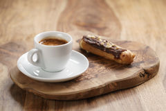 Fresh espresso and eclair with hazelnuts Royalty Free Stock Image
