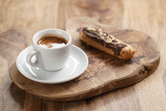 Fresh espresso and eclair with hazelnuts Royalty Free Stock Photos