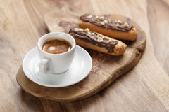 Fresh espresso and eclairs with hazelnuts Stock Photography