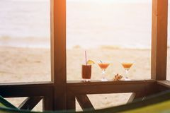 Fresh exotic cocktails on wooden edge. Shell lying between glasses. Cola with straw and lemon. Edge of house. View at. Ocean royalty free stock photo