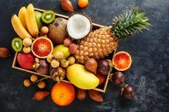 Fresh exotic fruit in a box. Golden pineapple, blood orange, coconut, mini bananas, longan, Salak. Thai fruits stock image