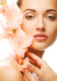 Fresh face with gladiolus flowers in her hands Royalty Free Stock Photos