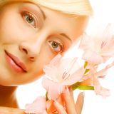 Fresh face with gladiolus flowers in her hands Stock Image