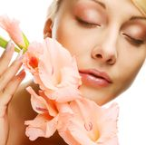Fresh face with gladiolus flowers in her hands Royalty Free Stock Photography
