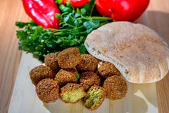 Fresh falafel balls, pita bread and red pepper on a wooden cutting board royalty free stock photo