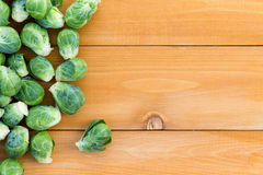 Fresh farm brussels sprouts with copy space. Fresh farm brussels sprouts arranged to the side on a wooden garden table, overhead with copy space Stock Photo