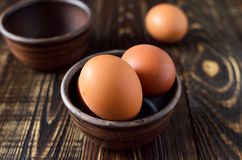 Fresh farm eggs in the bowl. On a wooden rustic background Stock Photo