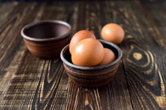 Fresh farm eggs in the bowl. On a wooden rustic background Stock Images