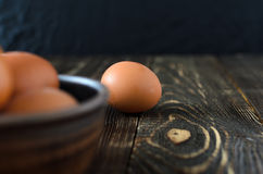 Fresh farm eggs in the bowl. On a wooden rustic background Royalty Free Stock Image