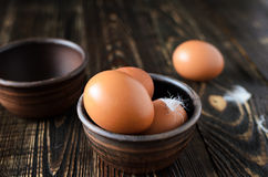 Fresh farm eggs in the bowl. On a wooden rustic background Stock Photos