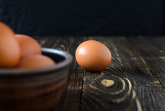 Fresh farm eggs in the bowl. On a wooden rustic background Stock Image