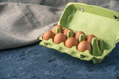Fresh farm eggs in green tray, on beautiful dark background. Home eco-friendly products. Brown fresh farm eggs in green tray, on beautiful dark background. Home Royalty Free Stock Photo