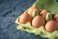 Fresh farm eggs in green tray, on beautiful dark background. Home eco-friendly products. Brown fresh farm eggs in green tray, on beautiful dark background. Home Stock Photo