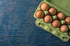 Fresh farm eggs in green tray, on beautiful dark background. Home eco-friendly products. Brown fresh farm eggs in green tray, on beautiful dark background. Home Royalty Free Stock Photos