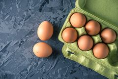 Fresh farm eggs in green tray, on beautiful dark background. Home eco-friendly products. Brown fresh farm eggs in green tray, on beautiful dark background. Home Royalty Free Stock Photography