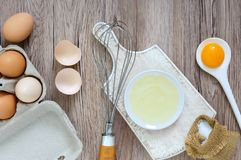 Fresh farm eggs on a wooden rustic background. Separated egg white and yolks, broken egg shells. Stock Photography