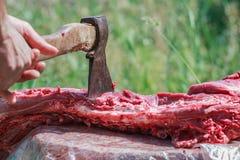 Fresh farm sheep carcase chopping by axe in man hand Stock Photos