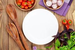 Fresh farmers tomatoes and basil with kitchen utensils. Fresh farmers tomatoes and basil on wood table with empty plate for copy space Stock Photos
