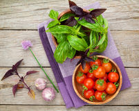 Fresh farmers tomatoes and basil. On wood table Stock Photos