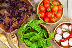 Fresh farmers tomatoes and basil. On wood table Stock Photo