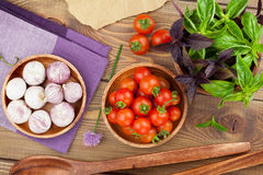 Fresh farmers tomatoes and basil. On wood table Royalty Free Stock Images