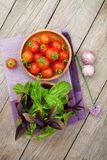 Fresh farmers tomatoes and basil. On wood table Stock Photography
